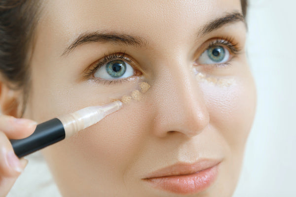 Woman applying concealer to take care of dark spots.