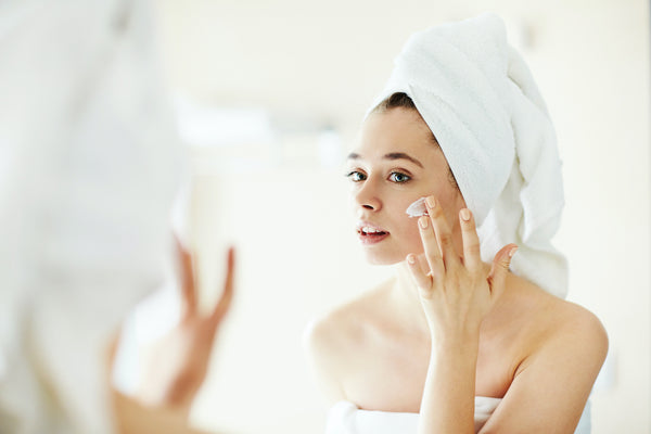 Women prepares face with moisturizer.
