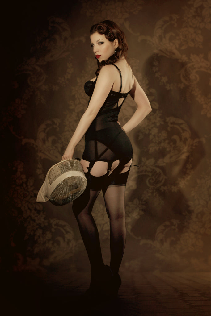 Retro black lace and powernet corselette with vintage sepia background and fencing accessories