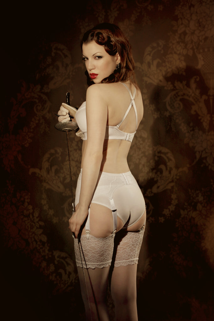Retro deep white garter belt with lace and 6 suspender straps on vintage sepia background and fencing foil