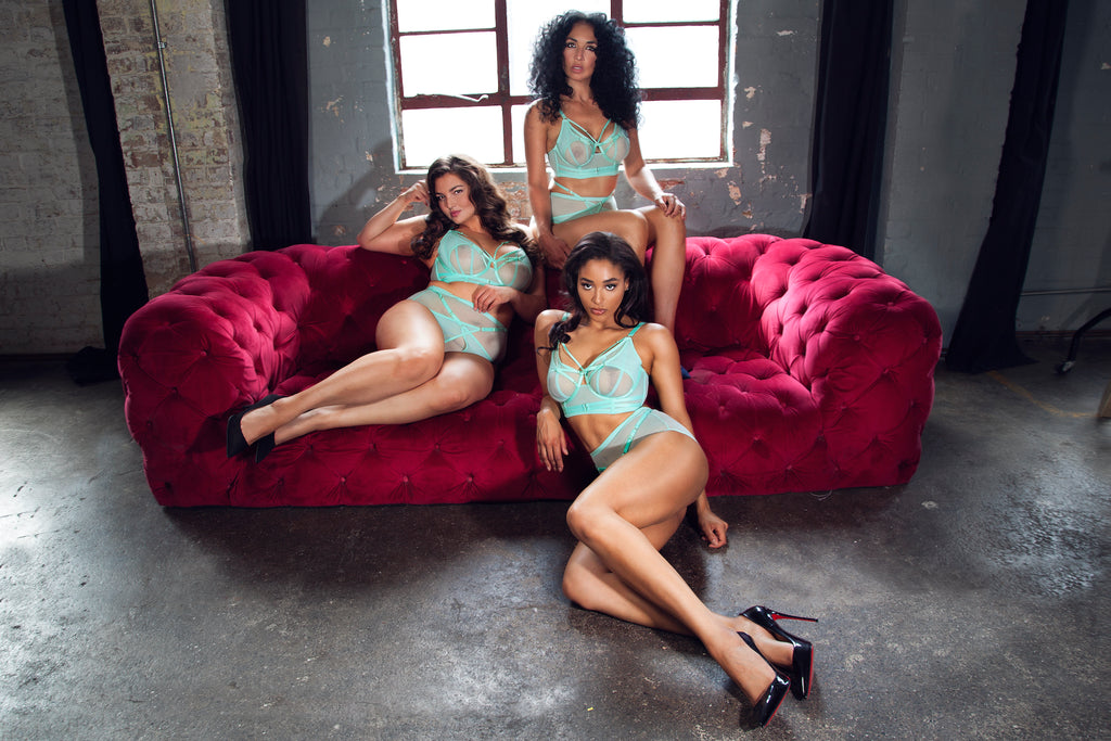 3 including a plus size and full busted woman wear mint green mesh strappy lingerie  sat on a red velvet sofa