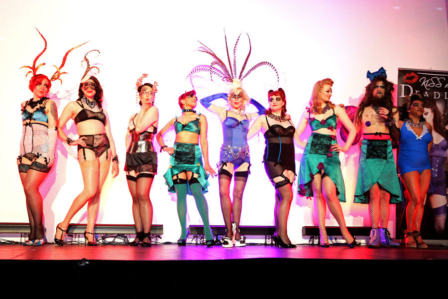 A catwalk of Kiss Me Deadly fans featuring eight women and one man in customised lingerie outfits and hats.