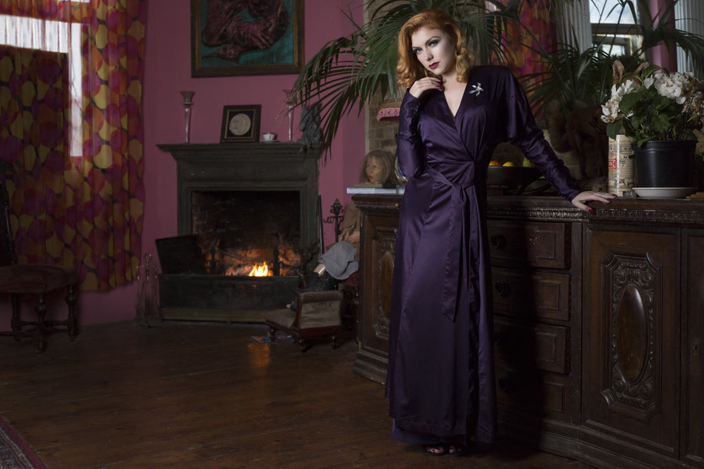 A model in a plum satin full length 1930's style lounges against a fireplace and wooden dresser
