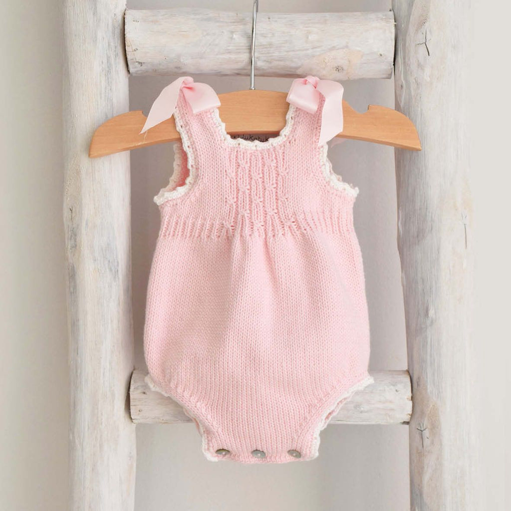 Pink knitted romper with bows