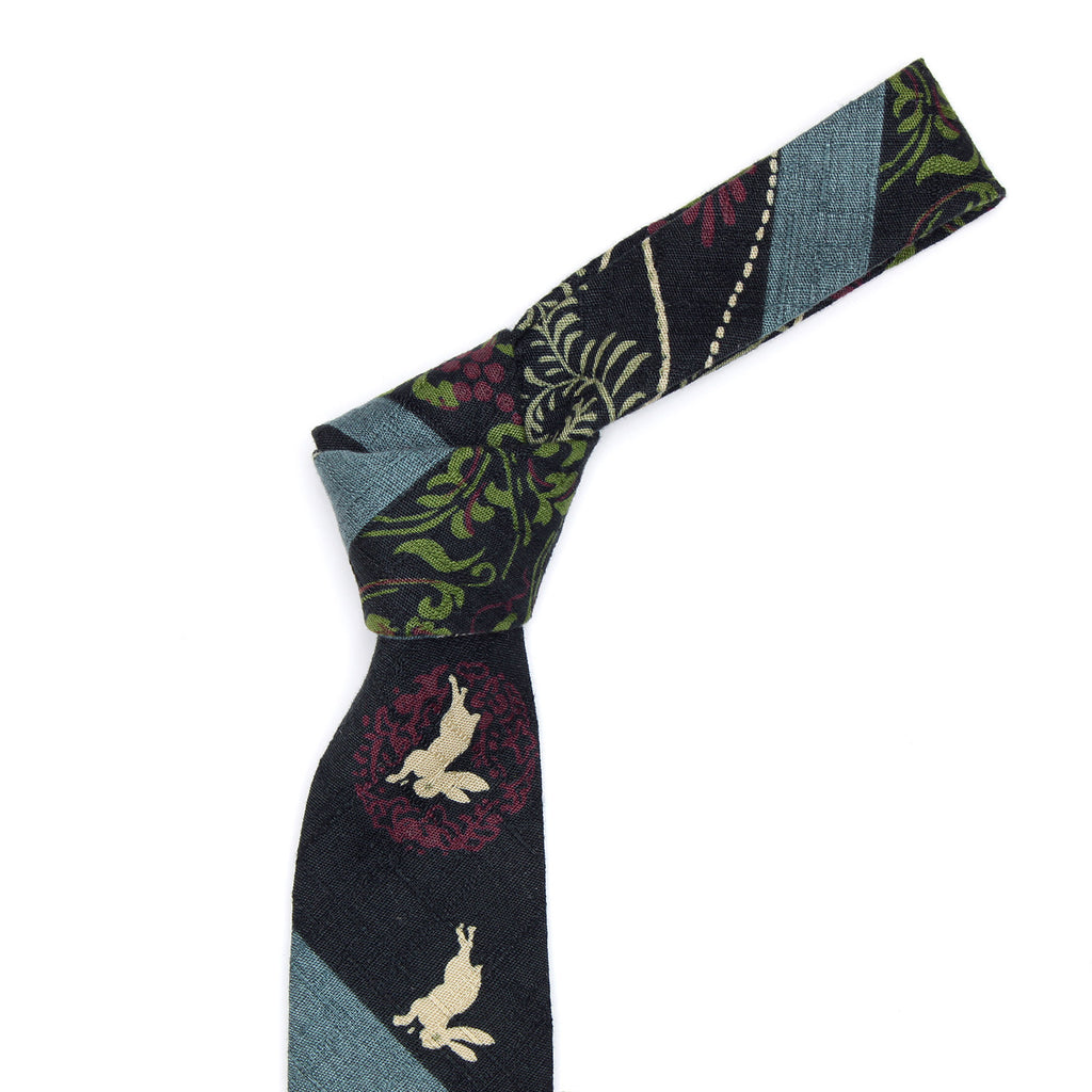 The White Usagi necktie is a thin necktie from Olaf Olsson made from Japanese fabric with a delicate print of rabbits and chrysanthemums from Japan. It is beautiful neckwear.