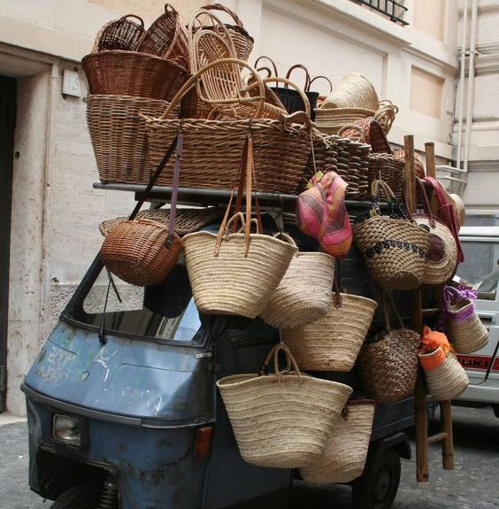 Baskets in San Tropez hanging from a small blue vintage truck