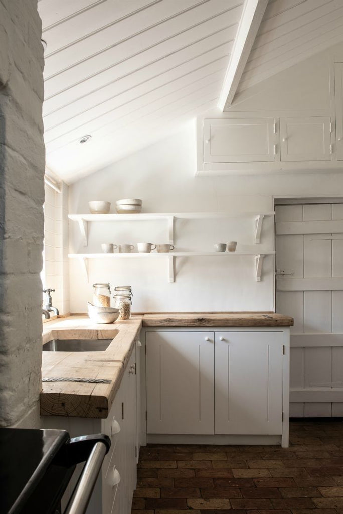 White rustic kitchen with sloped ceilings and butcher block countertops