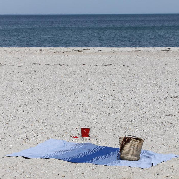 Blue stripes cotton beach throw blanket laying on the sand with a classic red enamel beach bucket.