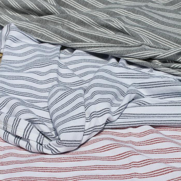 A pile of striped cotton throw or beach blankets. Made in USA. Choose from red, blue, or grey stripes. .