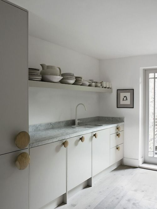 White kitchen with open shelving and big wooden door pulls