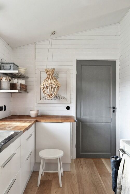White kitchen with grey door and beaded chandelier