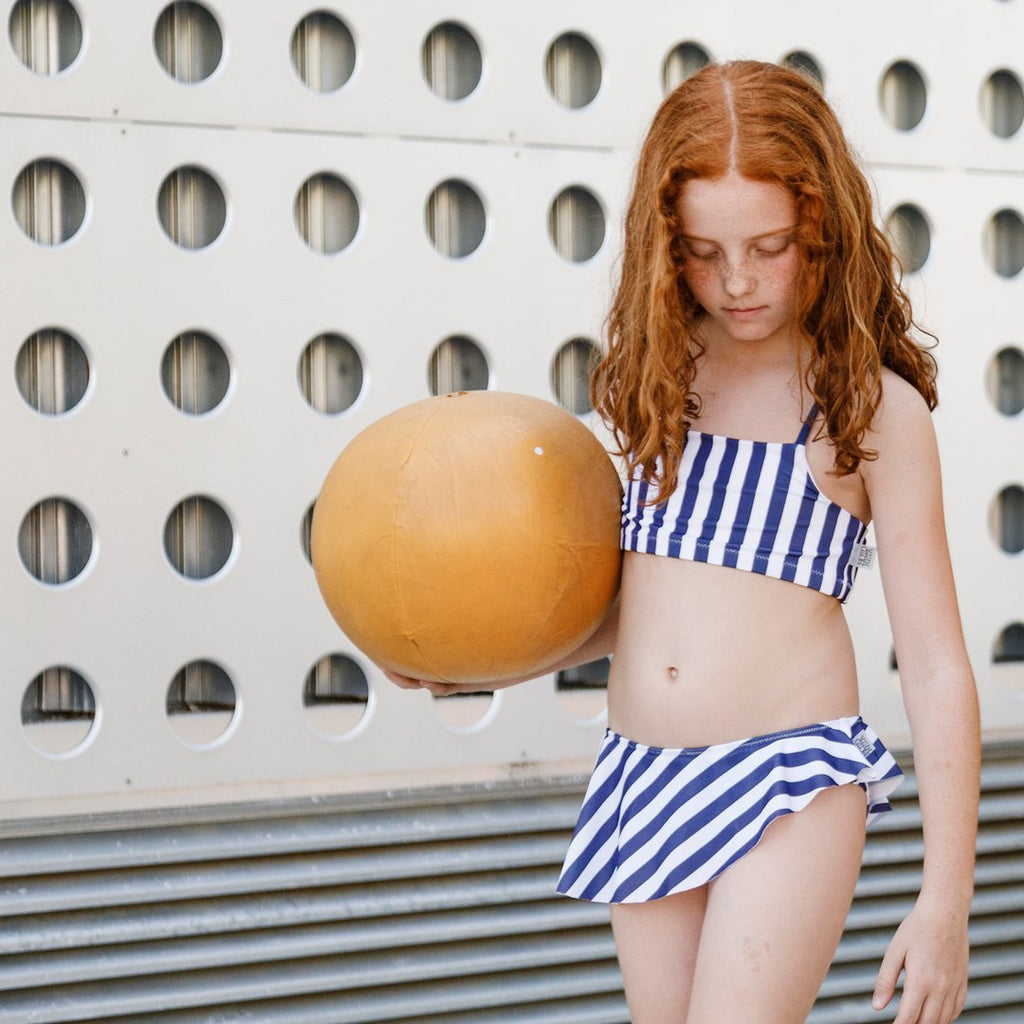 Girl wearing bikini in blue and white stripes  with a criss-cross top and a ruffled bottom by Motoreta