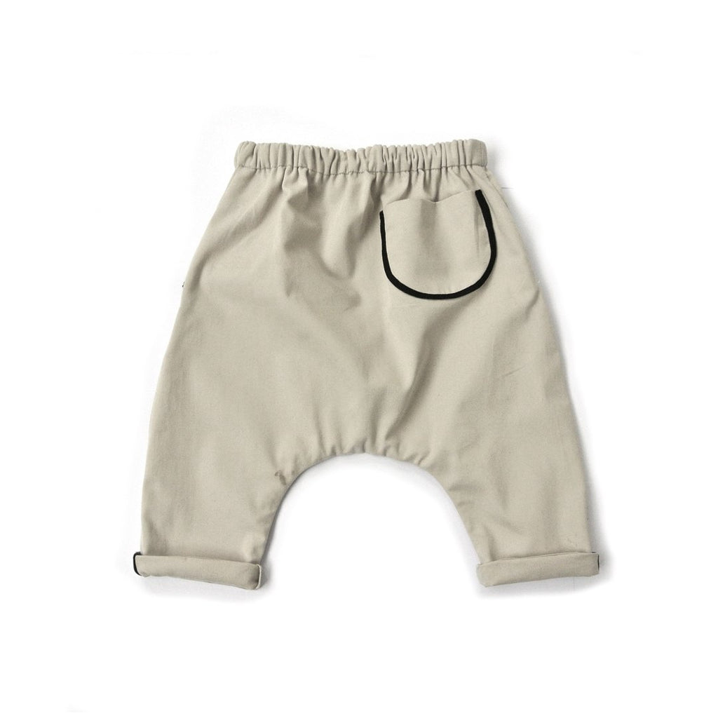 Back of cotton Unisex baby loose trousers in almond with two front pockets and one back pocket, with contrast black linings