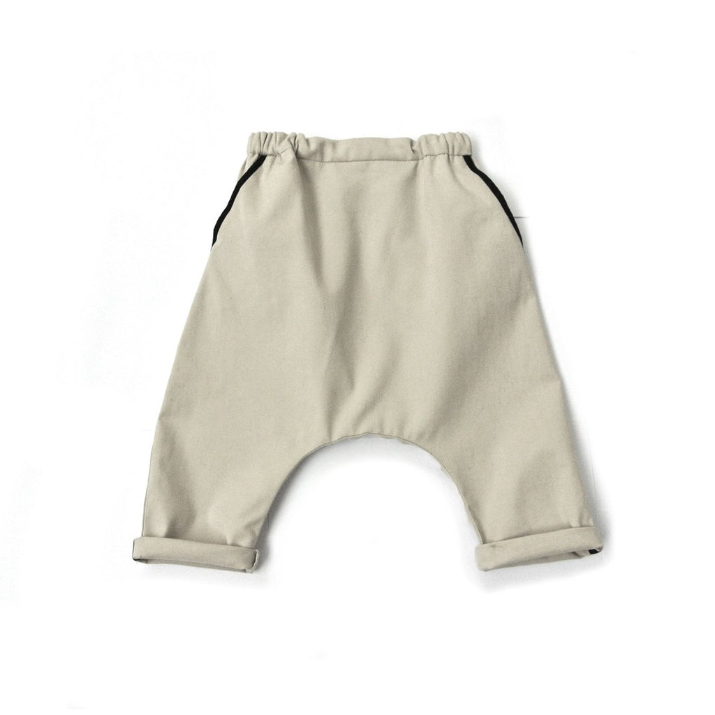 Cotton Unisex baby loose trousers in almond with two front pockets and one back pocket, with contrast black linings