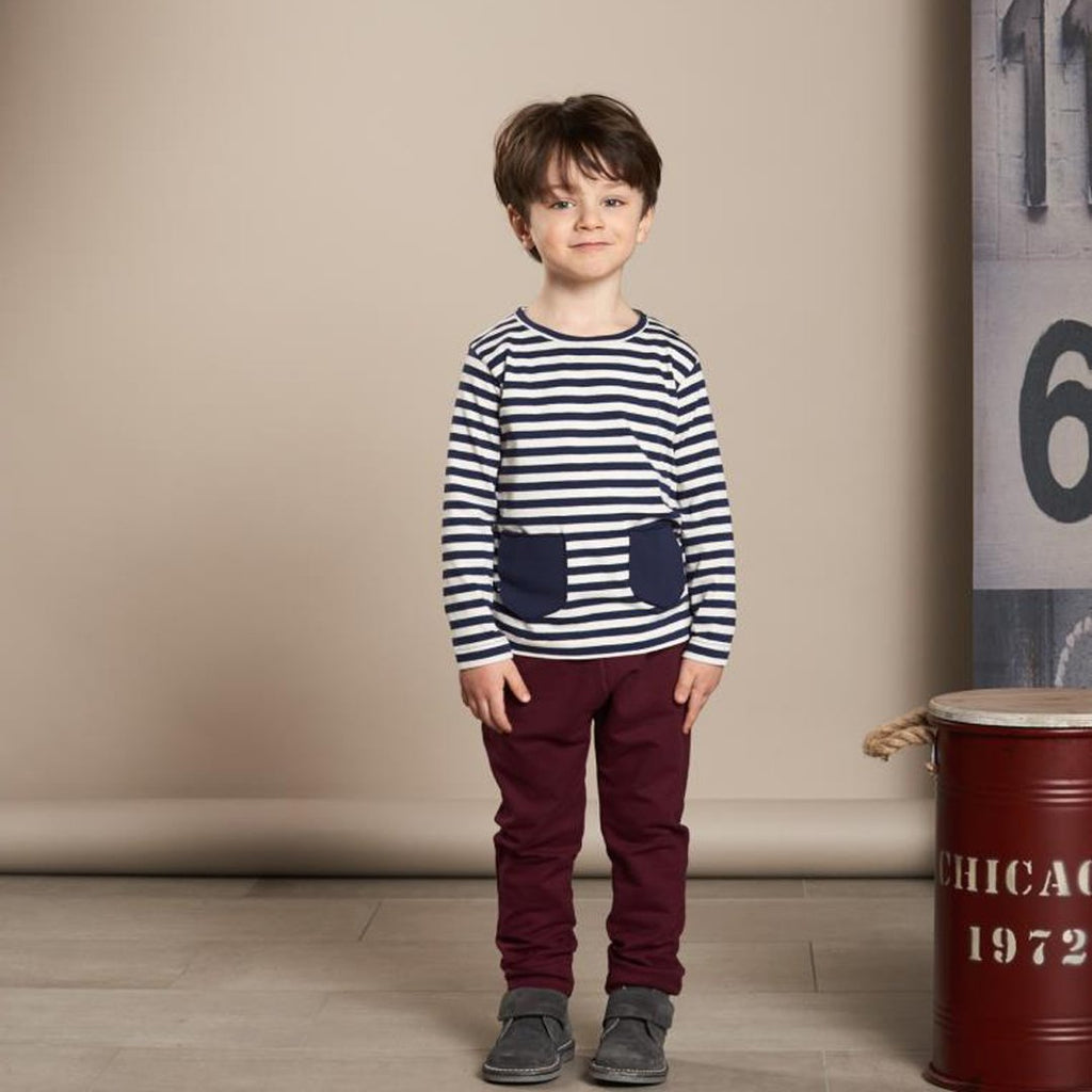 Boy wearing long-sleeve baby t-shirt in blue and white stripes with two cute front pockets by Il Guardarobino