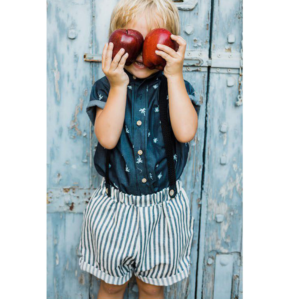 Boy wearing pull-on shorts with removable suspenders in striped denim fabric by Chichirikids