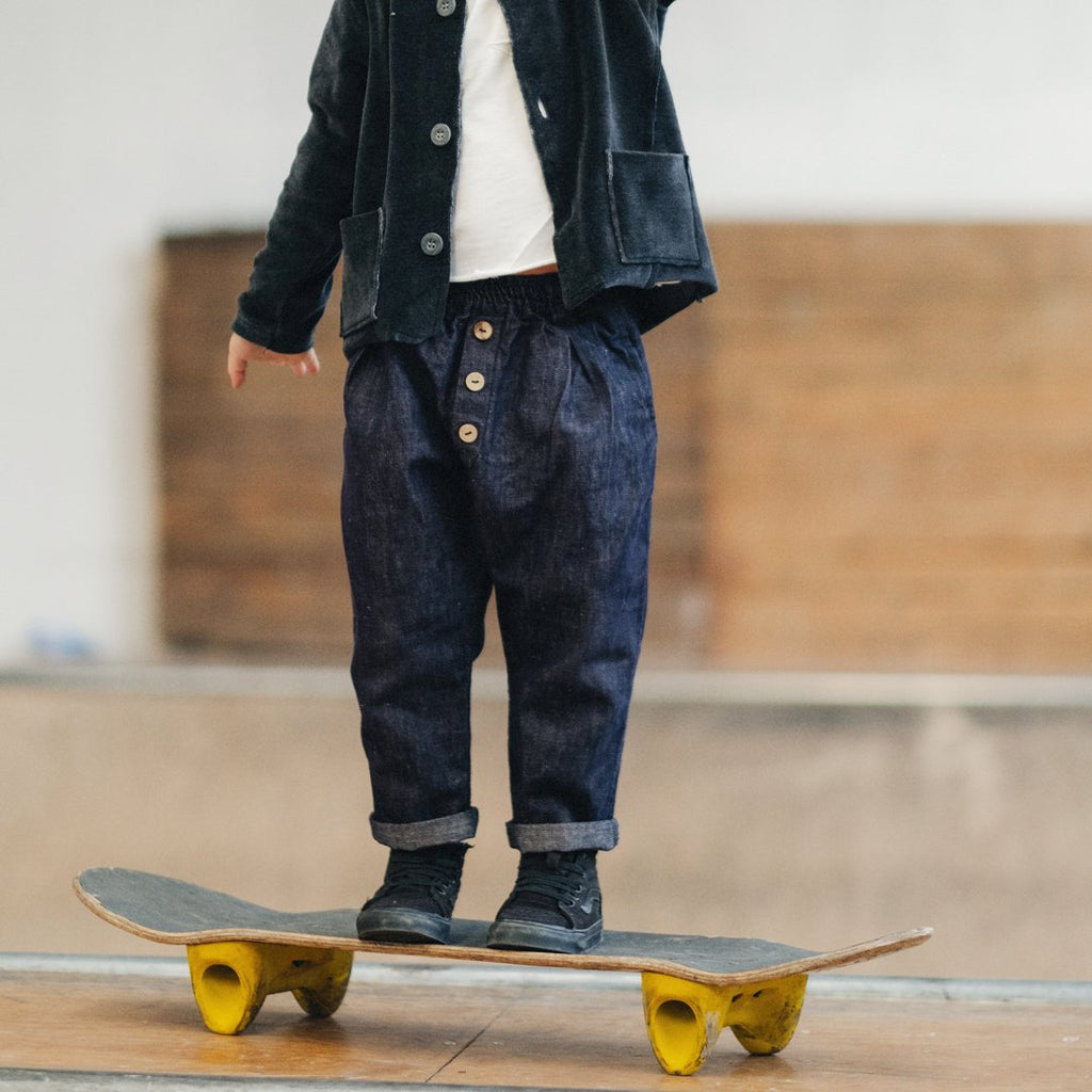 Boy wearing dark blue denim jeans featuring coconut buttons on the front and a loose, comfortable fit by Chichirikids