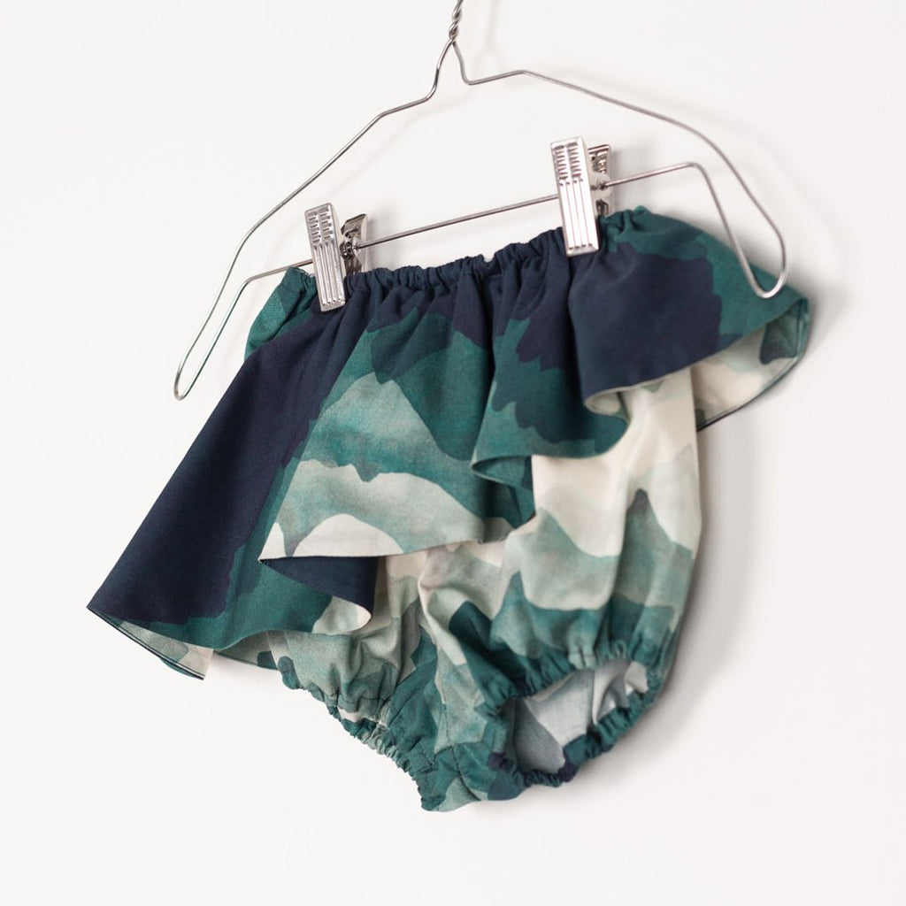 Detail of baby bloomers with a landscape print, featuring ruffles and an elastic band by motoreta