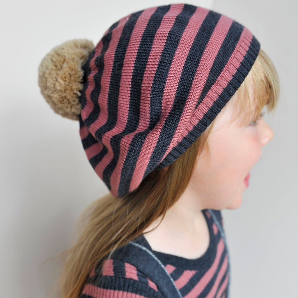 kid in Seamless toddler and kids pink beanie in Extra Fine Merino Wool with a big contrasting pom-pom i100% Extrafine Merino Wool by mabli knits