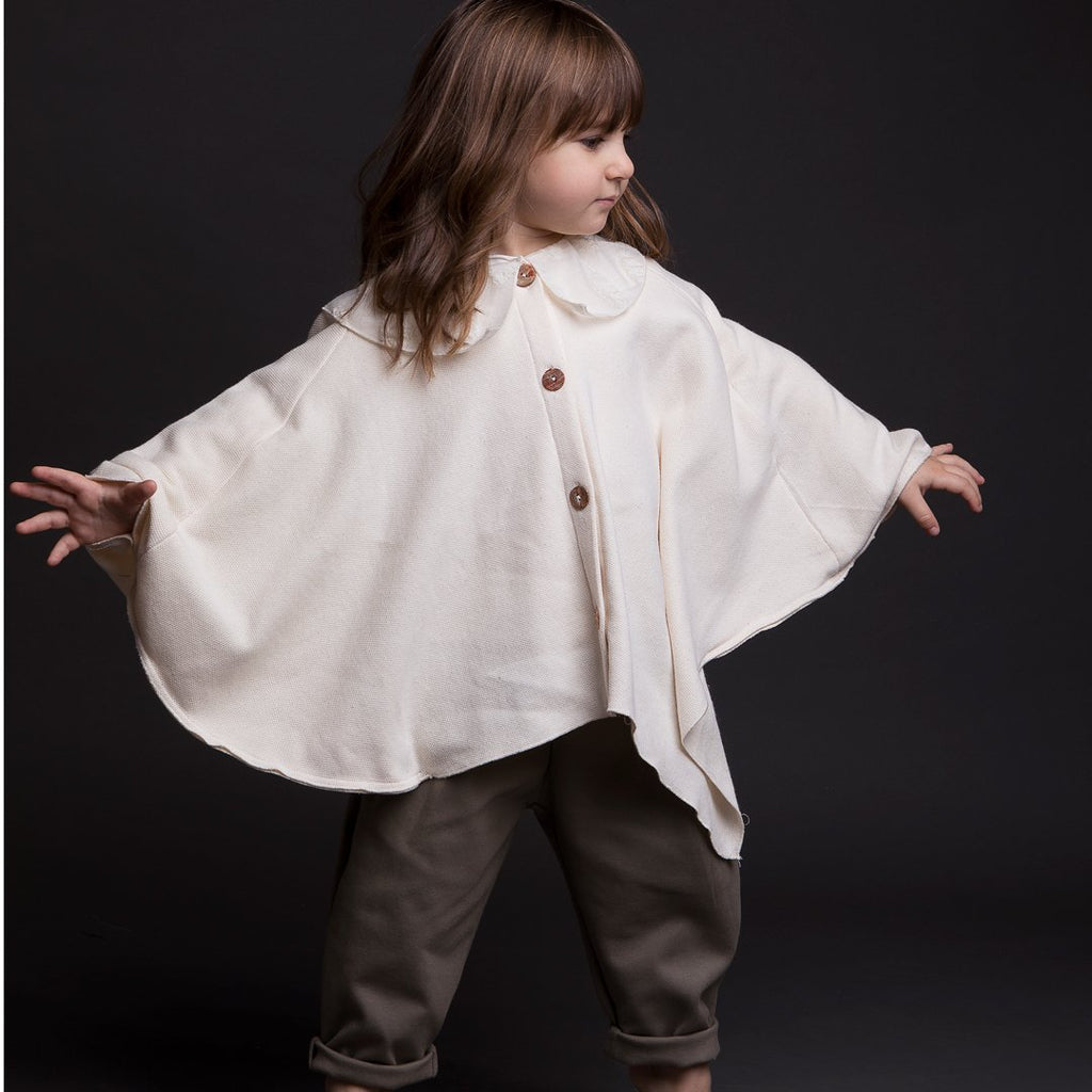 Girl twirling in cloak in a nude color for girls with a tone on tone fancy collar and front buttons.