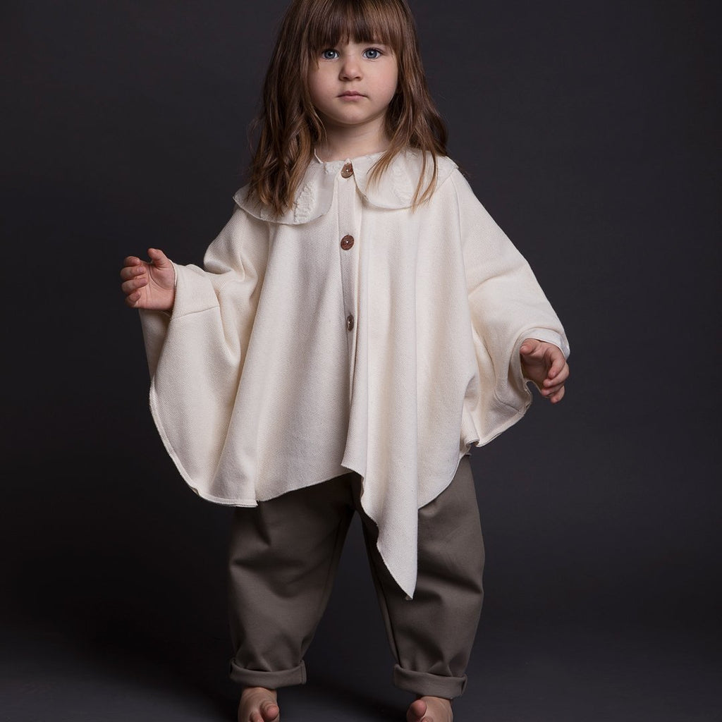 Girl wearing luxury cloak in a nude color for girls with a tone on tone fancy collar and front buttons.