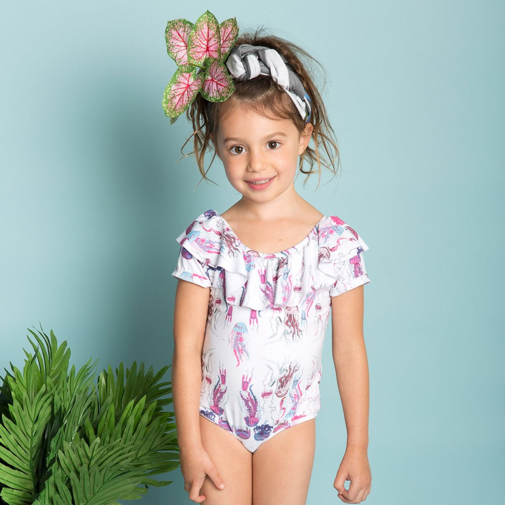 Girl wearing ne-piece bathing suit for girls, with sort sleeves and ruffles and jellyfish prints by EFVVA