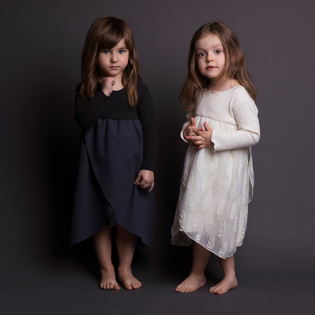 Girls wearing layered dresses in cotton and wool, the top layer fabric has oval details.