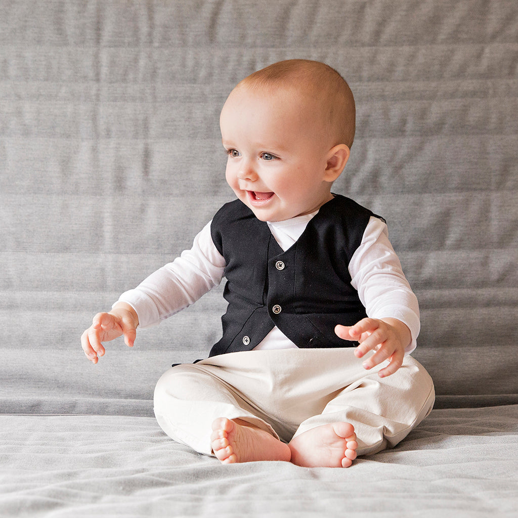 Baby boy wearing an elegant baby waistcoat in black with front buttons and opening by Treehouse