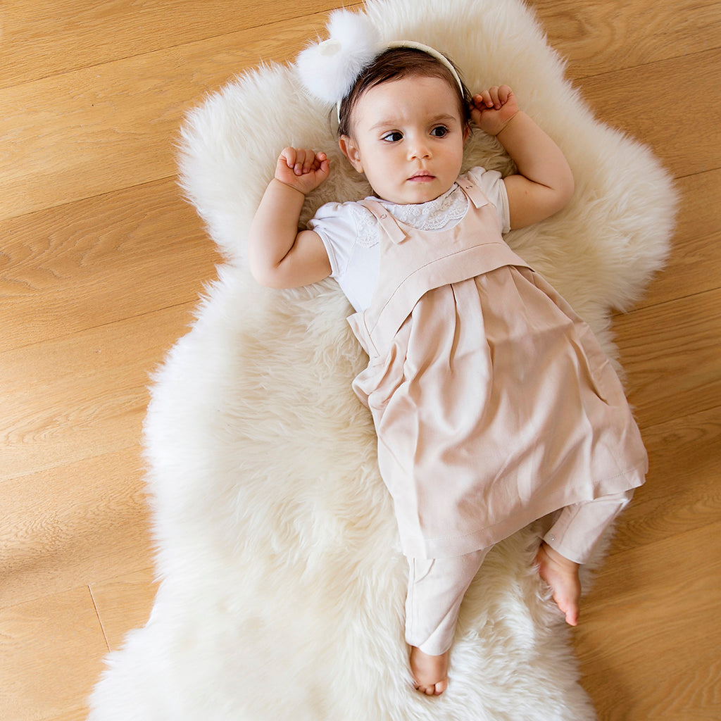 Baby girl in blush Apron overall by Treehouse