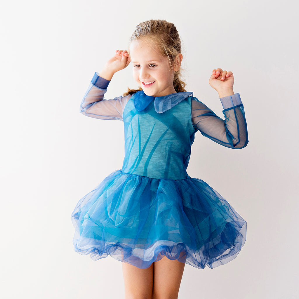 Girl in Dress in different shades of blue with a crinkle effect. Long-sleeve and knee-length, and costrasting colors on sleeves and neck by Nikolia