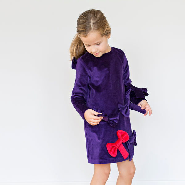 Girl wearing Beautiful deep purple dress in super trendy velvet, with cute large bow appliques all over by Nikolia
