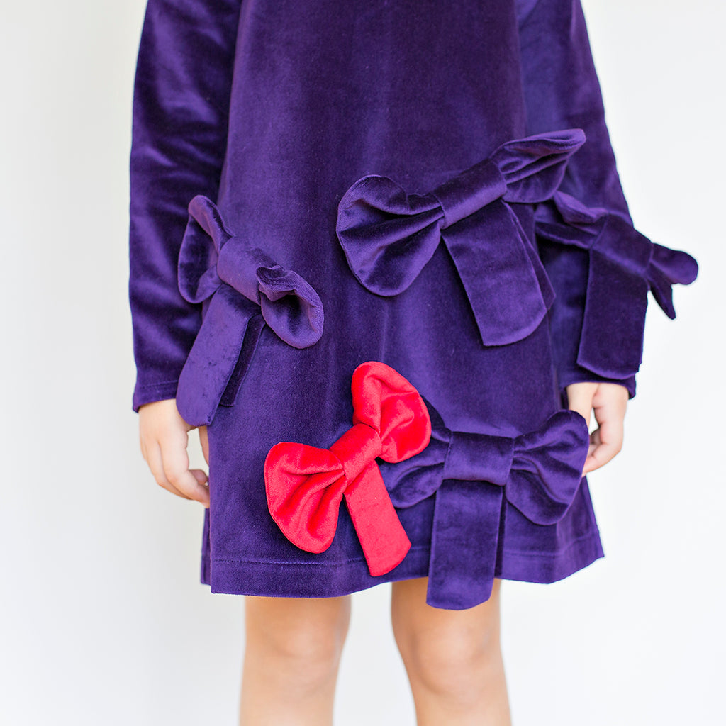 Detail of deep purple dress in super trendy velvet, with large bow appliques all over by Nikolia