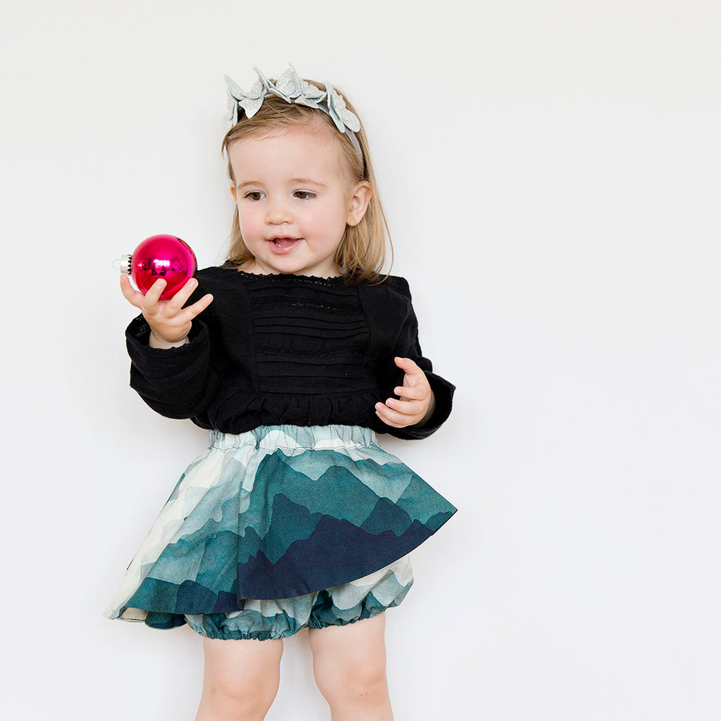 Toddler wearing bloomers with a landscape print, featuring ruffles and an elastic band by motoreta