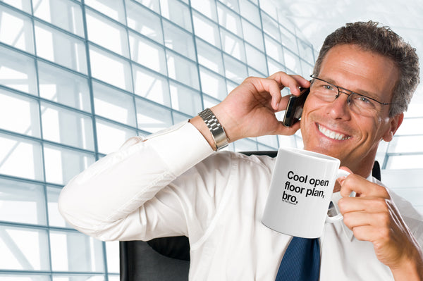 "Stock photo, office setting, Office bro on phone with mug that says, ""cool open floor plan, bro."""