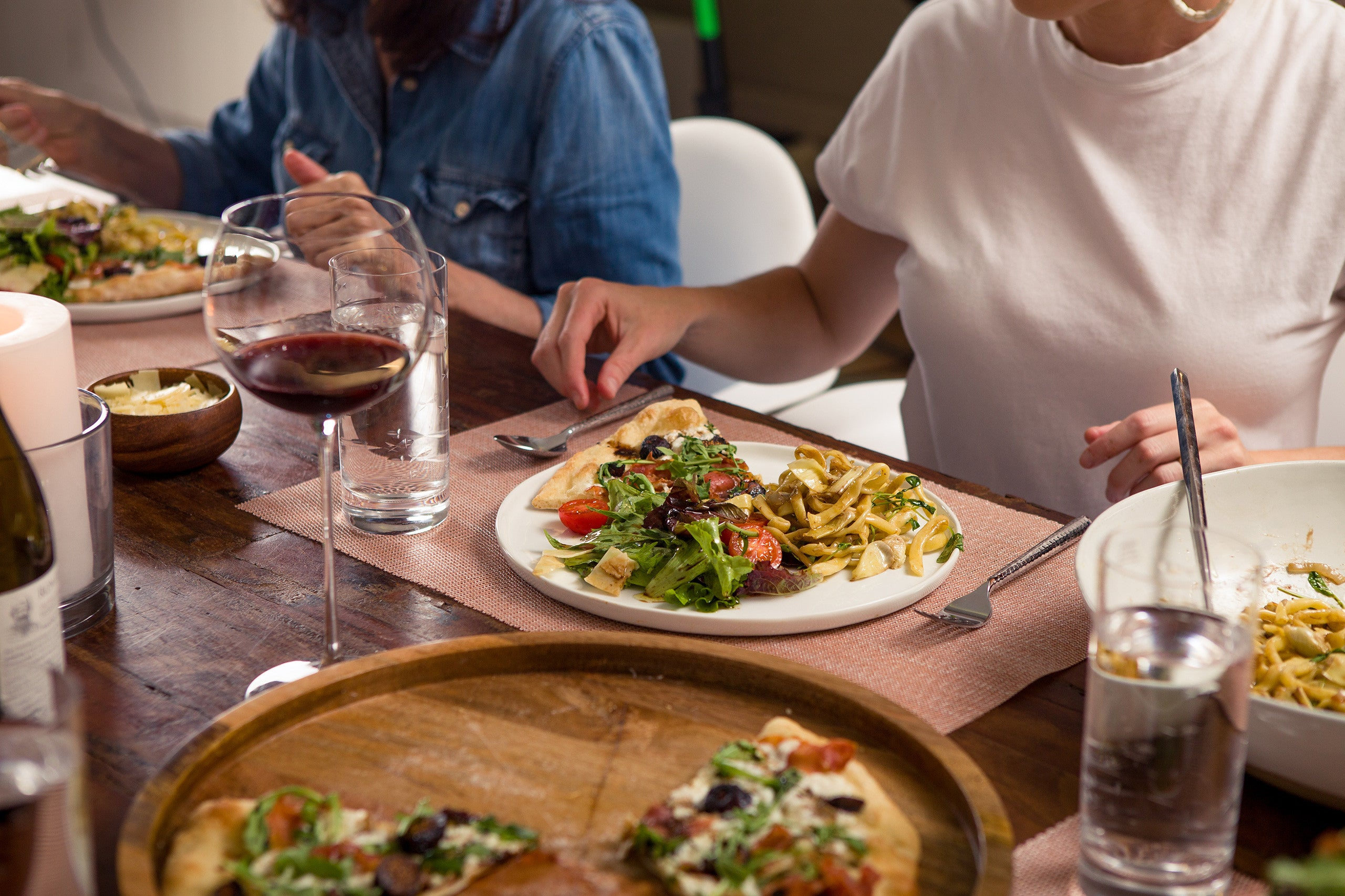 A family seated around a table, enjoying a dinner from a Vero Pizza and Pasta meal kit