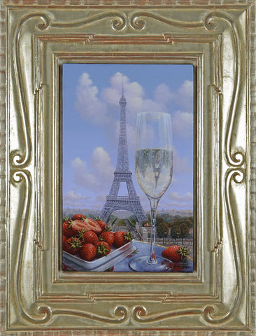 A Glass of Champagne and strawberries with the view of the Eiffel Tower and blue skies in the background.