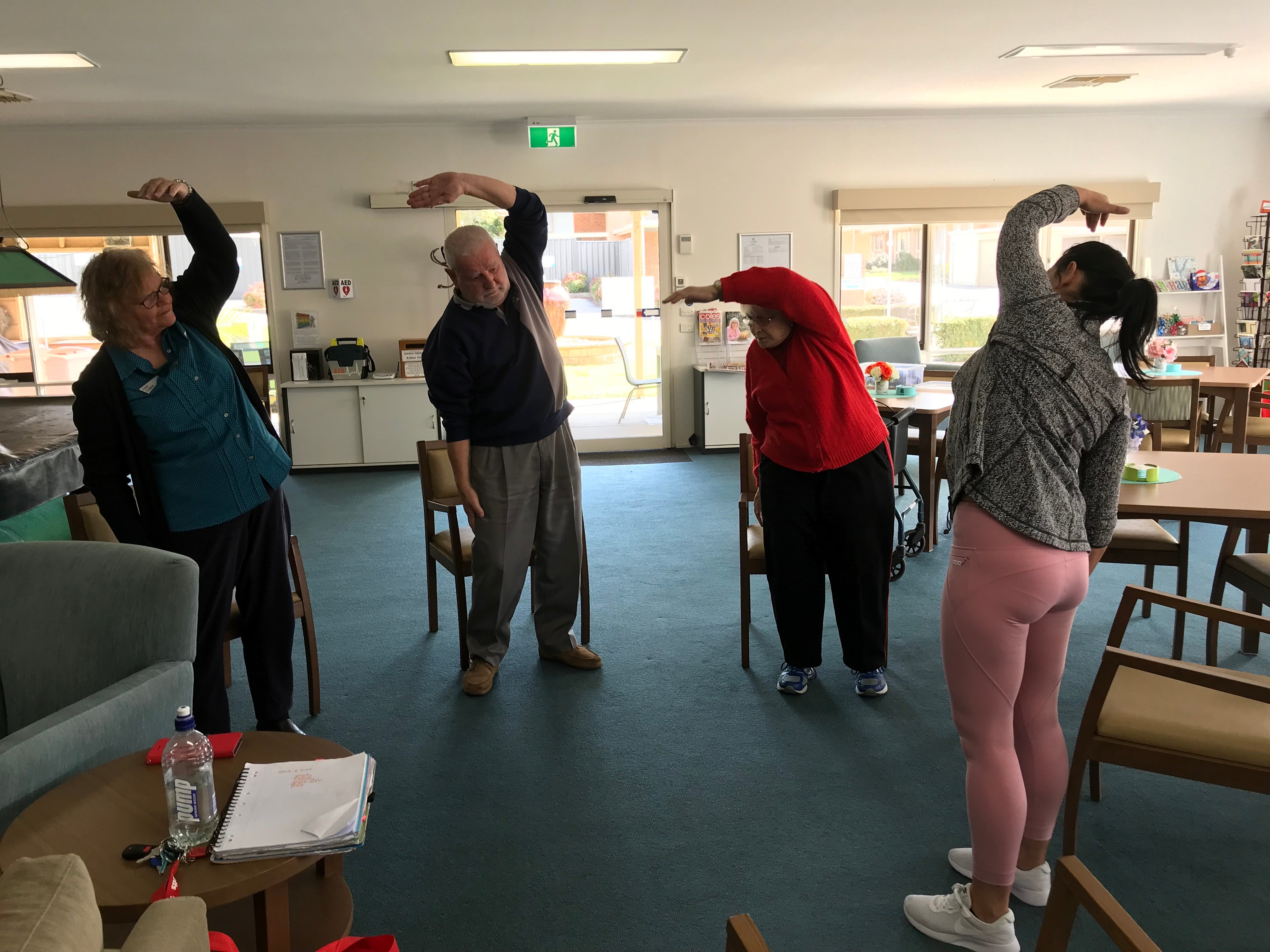Image of participants in exercise program streching overhead