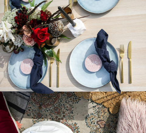 table setting with gold cutlery and blue pottery plates by exotic soirees marquee hire