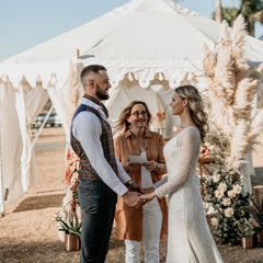 bride and groom ceremony and celebrant standing in front of a luxury marquee from exotic soirees hire on the gold coast