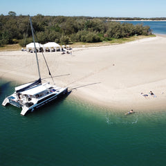 catamaran moored on an island with two Arabian marquee tents from exotic soirees hire on the gold coast