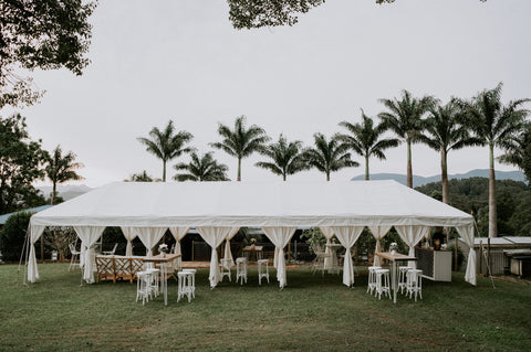 Luxury Arabian wedding marquee in white with a corporate setup feel with furniture and a bar on the grass