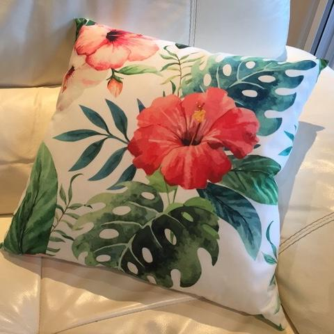 Tropical cushion with green leaves and orange hibiscus flower