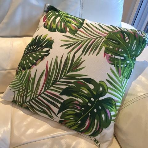 Cushion for hire showing tropical palm prints on a white background