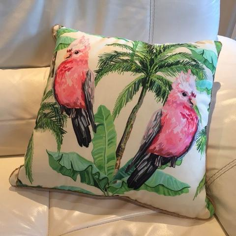 Cushions with green tropical palms and pink galah parrots