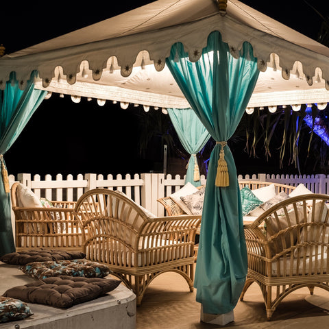 Turquoise Arabian Tents on display at night under beautiful lights with cane furniture for a corporate party