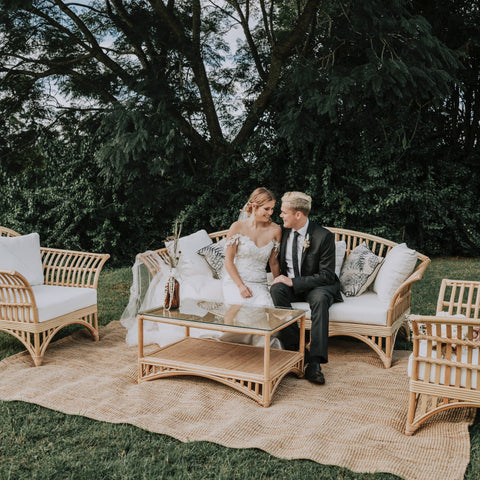 cane sofa setting with jute rug and a bride and groom sitting down