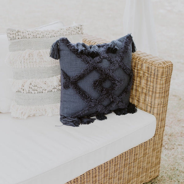 Navy blue cushion with frills and tassels in a summer cane furniture styled shoot