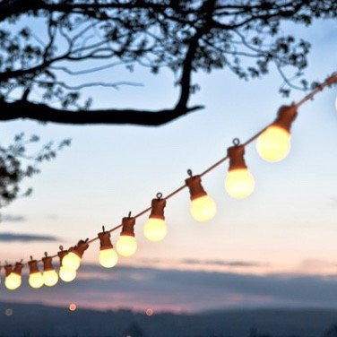 stunning festoon lights glowing in front of a backdrop of setting sun and mountains to hire from exotic soirees luxury marquees on the gold coast