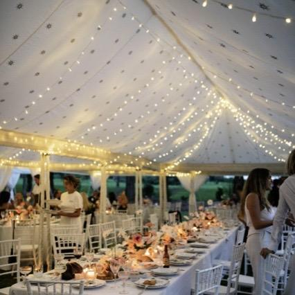 fairylights in the roof of a wedding marquee with table and flowers