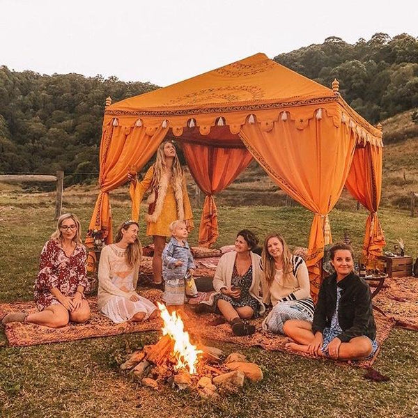 luxury yellow cabana on a farm with fire and friends celebrating